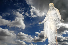 Jesus and Clouds. Jesus standing in white and gray storm clouds in blue sky with rays of light Royalty Free Stock Image