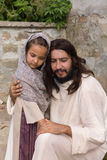 Jesus comforting a little girl. Biblical scene when Jesus says, let the little children come to me, blessing a little girl. Historical reenactment at an old Stock Photos