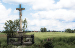 Jesus on the cross in the country field. Sculpture of the Jesus in the old country road chapel Royalty Free Stock Photos