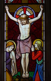 Jesus on the cross. Detail of victorian stained glass church window in Fringford depicting Jesus nailed to the cross with St. Mary and St. John at the feet of Stock Photos