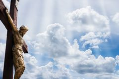 Jesus on a cross against blue sky with white clouds Royalty Free Stock Photo