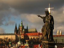 Jesus with cross against Prague Castle. At the Charles Bridge in Prague, Europe. A statue of Jesus carrying a golden cross pointing toward Prague castle - the Royalty Free Stock Photos
