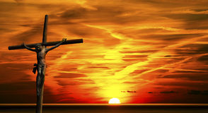 Jesus on the Cross at Sunset. The cross (bronze and wood) - Jesus on the Cross at beautiful sunset over the sea with cloudy sky Royalty Free Stock Photo