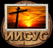 Jesus Cross at Sunset in Russian Language. Cross silhouette at sunset in a old photo frame on a section of tree trunk and text Jesus in russian language isolated Stock Images