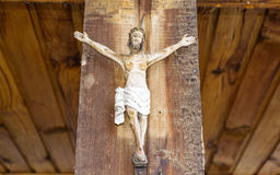 Jesus crucified. Small Jesus figurine  crucified on a wooden background Royalty Free Stock Images