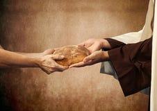 Jesus dá o pão a um mendigo. Imagem de Stock