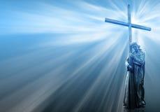 Jesus, der ein Kreuz auf blauem Hintergrund anhält Lizenzfreie Stockbilder