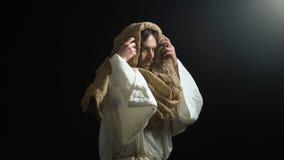 Jesus in der Robe, die aus Dunkelheit herauskommt und Hände, Aufruf an Gott, Glaube anhebt stock video