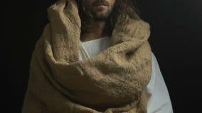 Jesus in der Robe, die das Brot, helfend zeigt, Leute, Gottgüte und Gnade verhungernd stock footage