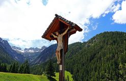 Jesus diagram på ett träkors i en kyrkogård i bergen Royaltyfri Foto