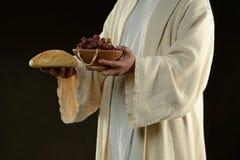 Jesus die een brood en druiven houden stock foto