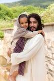 Jesus die een klein meisje houden royalty-vrije stock fotografie