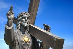 Jesus die een kruis op blauwe achtergrond houdt Stock Foto's