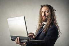Jesus die zijn laptop controleren stock afbeelding