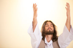 Jesus with eyes closed. Raising hands to heaven Royalty Free Stock Photography