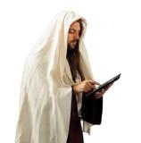 Jesus gebruikt de tablet Stock Afbeelding