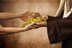 Jesus ger bröd och druvor arkivbild