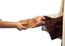 Jesus ger brödet till en tiggare. Arkivbild