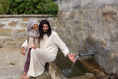Jesus with a girl at a water well. Biblical scene when Jesus says, let the little children come to me, blessing a little girl. Historical reenactment at an old Stock Image