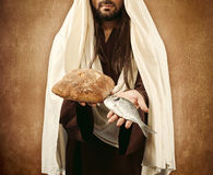 Jesus gives bread and fish. On beige background Royalty Free Stock Photos