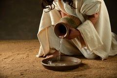 Jesus hällande vatten från en krus royaltyfri fotografi
