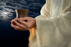 Jesus händer som rymmer koppen arkivfoto