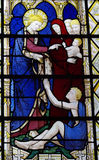 Jesus helping a poor man (stained glass) Royalty Free Stock Photography