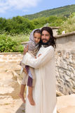 Jesus holding a child. Biblical scene when Jesus says, let the little children come to me, blessing a little girl. Historical reenactment at an old water well Stock Photo