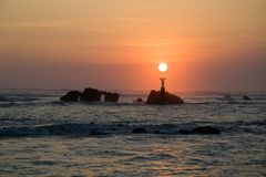 Jesus holding the sun. The sun sets over a statue of Jesus out in the ocean in El Salvador Royalty Free Stock Photos