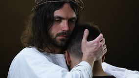 Jesus hugging young miserable man and looking at camera, forgiving sins. Stock footage stock video