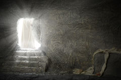 Jesus Leaving Empty Tomb. While light shines from the outside royalty free stock image