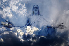Jesus and Light. Jesus standing in white and gray storm clouds in blue sky with rays of light Royalty Free Stock Image