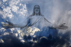 Jesus and Light. Jesus standing in white and gray storm clouds in blue sky with rays of light Stock Photography
