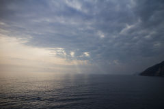 Jesus light through clouds. Jesus light radiate through clouds to the sea of Potoverence. The ship travels with traces in sunset. Heavy and dark clouds seems to Stock Image