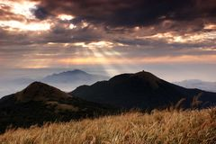 Jesus light in Yangmingshan National Park. The Jesus light is passing over clouds and shinning on the top of Mt and sea with flowers as foreground.Taipei is my Stock Photo
