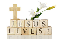 Jesus Lives!. Wooden alphabet blocks that spell out Jesus Lives! with a cross above on the left and Easter lillies to the right.  On a white background Stock Image