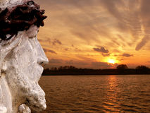 Jesus looking at the sunset. A statue of jesus against sunset landscape Royalty Free Stock Photography