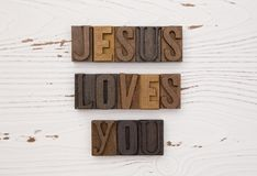 Jesus Loves You. On a distressed white wood table Stock Photo