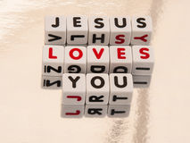 Jesus loves you. Text Jesus loves you inscribed on small white cubes in uppercase letters; message of the Gospel, good news Stock Photography