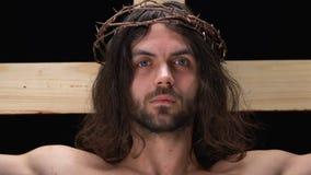 Jesus na coroa de espinhos crucificados na cruz que olha a câmera, salvar dos pecados filme