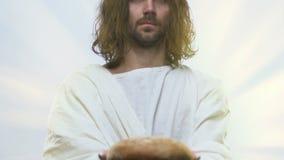Jesus na veste branca que alcança para fora as mãos com pão, bênção e ajuda aos povos video estoque