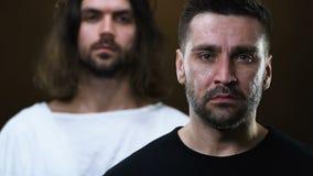 Jesus na veste que põe a mão sobre a cabeça e o ombro de grito do homem, curando da doença filme