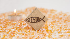 Jesus name in Christian symbol. Wood object and the shape of a fish, which was an early symbol of Christianity, on an orange background and a candle Stock Photography