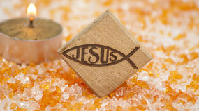 Jesus name in Christian symbol. Wood object and the shape of a fish, which was an early symbol of Christianity, on an orange background and a candle Stock Images