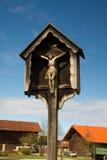 Jesus på korset i by Arkivbild