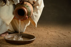 Jesus Pouring Water. From jug over dark background Royalty Free Stock Photo
