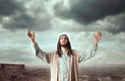 Jesus praying with his hands up against cloudy sky. Jesus Christ in white robe praying with his hands up against cloudy sky. Strong faith in God, christianity Stock Photo