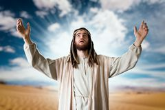 Jesus praying with his hands up against cloudy sky. Jesus Christ in white robe praying with his hands up against cloudy sky. Strong faith in God, christianity Stock Photos