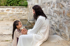 Jesus praying with a little girl. Biblical scene when Jesus says, let the little children come to me, blessing a little girl. Historical reenactment at an old Stock Photos
