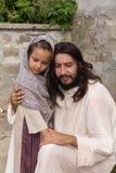 Jesus que consola uma menina fotos de stock